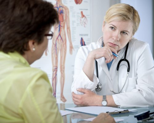 Doctor listening intently to middle aged female patient